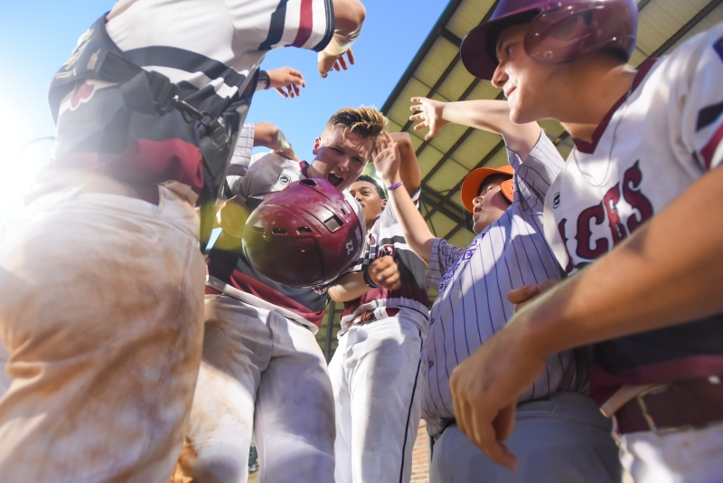 Chaison Miklich is swarmed by his Las Vegas, Nev., Post 40 teammates after scoring a run in game four of the 2018 American Legion World Series game at Keeter Stadium in Shelby, N.C., on Thursday, Aug. 16, 2018. Photo by Lucas Carter/The American Legion.
