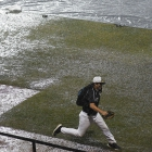 A member of Randolph County, N.C., Post 45 runs for cover as heavy rain postpones game 14 of The American Legion World Series on Monday, August 14, 2017 at Veterans Field at Keeter Stadium in Shelby, N.C. Photo by Matt Roth/The American Legion.