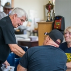 Medal of Honor recipient James C. McCloughan talks to friends Rich and Jan Woodard, members of Post 49, at a memorial dedication ceremony at The American Legion Edward W. Thompson Post 49 in South Haven, Mich. Photo by Robert Franklin/The American Legion