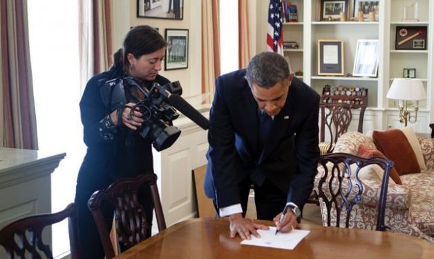 Videographer Hope Hall tapes President Barack Obama working on a document in the Chief