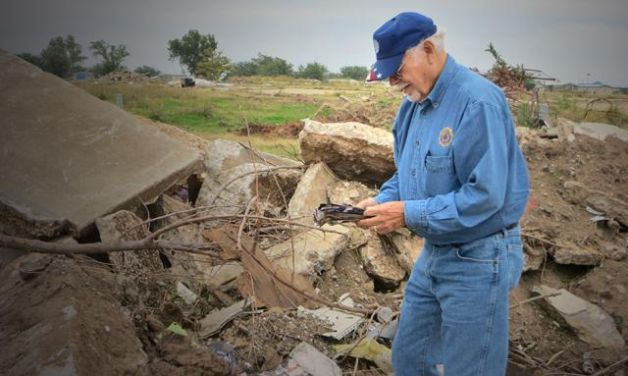 Joe DeLaCruz, chairman of the Department of Oklahoma's emergency relief program, looks over the tattered remains of a scrapbook in the aftermath of the tornado in Moore, Okla. (Photo by Henry Howard)