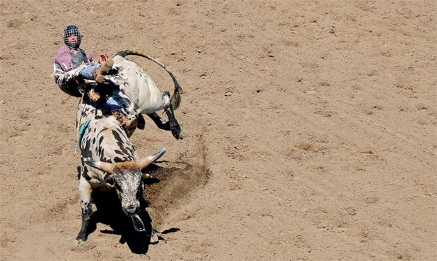 Keaton Mundy of Evansville, Wyo., is bucked from a bull during the Wyoming High School Rodeo